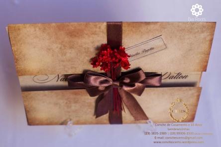 Convite de casamento com papel envelhecido de pergaminho e flores vermelhas com laco marrom